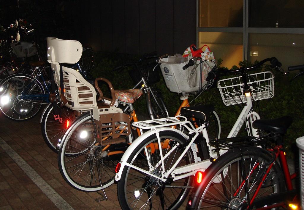 Bicicletes a la porta d'un super, cap al tard. Al cistell, part de la compra