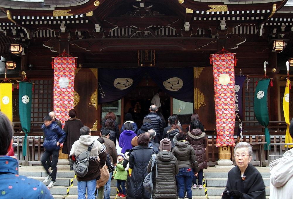 Gent fent cua a la porta d'un temple.