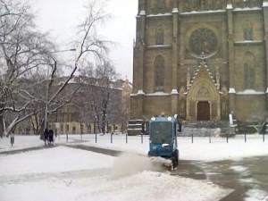Náměstí Miru avui al migdia. L'església de Santa Ludmila i una màquina municipal per treure la neu.